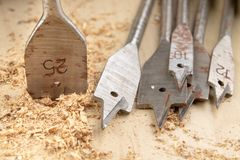 Drilling with a vane drill in chipboard. Carpentry work in a carpentry workshop. Light background stock photography