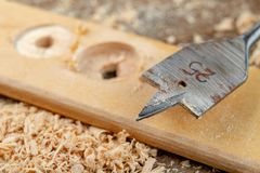 Drilling with a vane drill in chipboard. Carpentry work in a carpentry workshop. Light background stock image