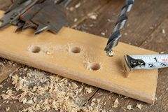 Drilling with a vane drill in chipboard. Carpentry work in a carpentry workshop. Light background royalty free stock images