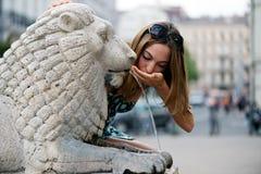 Drimnking vatten för ung kvinna från springbrunnen Arkivbild