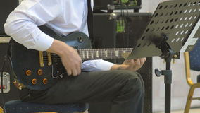 Dringende snaren op elektrisch gitaar speelclose-up 4k De musicus voert solo jazzoverleg uit stock footage