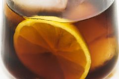 Drink. Red liqueur glass with ice cubes and lemon Stock Image