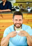 Drink it black with milk or cream hot or cold. Add flavor or sweeteners. Man bearded guy drinks cappuccino wooden table. Cafe. Cafe visitor smiling face enjoy stock photography