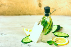 Drink in a bottle with a paper label, cucumber, lemon, and mint Stock Photos