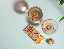 Drink champagne of wijn in twee elegante glazen en een bar van witte chocolade zachte blauwe achtergrond Conceptenminimalism stock foto's