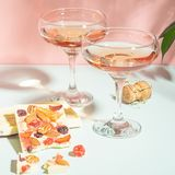 Drink champagne or wine in two elegant glasses and a bar of white chocolate. Gentle pink background bright sunlight. royalty free stock image