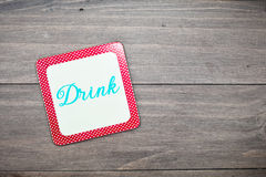 Drink coaster. A colorful retro drink coaster on a wooden surface Stock Photos