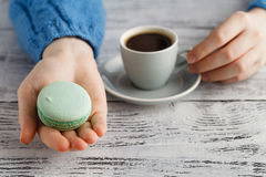 Drink coffee and hold macaroon. Girl drink coffee and hold macaroon Stock Images