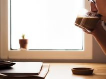 Drinking coffee on workspace desk with laptop by the window light. royalty free stock images