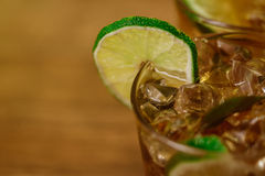 Drink concept - cocktail with cola ice cubes and lime Stock Photography