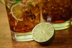 Drink concept - cocktail with cola ice cubes and lime Stock Photo