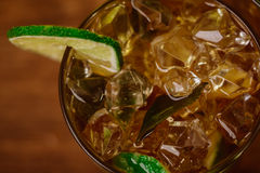 Drink concept - cocktail with cola ice cubes and lime Royalty Free Stock Photos