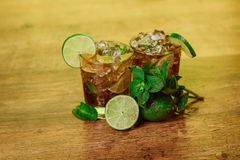 Drink concept - cocktail with  cola ice cubes and lime Stock Photos