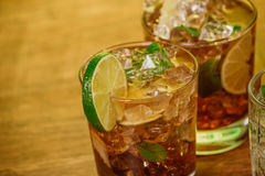 Drink concept - cocktail with  cola ice cubes and lime. Drink concept - cocktail with cola ice cubes and lime Royalty Free Stock Photo