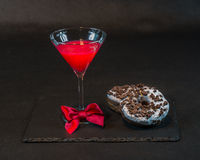 Drink cosmopolitan a glass of martini decorated with a red bow w. Ith two oreo doughnut on a black stone plate, the party set stock photo