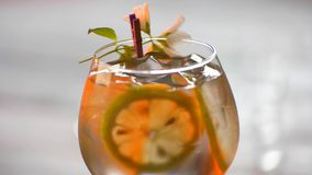 Drink decorated with a flower. Glass of beverage rotates. Sweet taste of tom collins. Coolness will relax you stock video