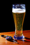 Drink and drive. Glass of light beer and car key Royalty Free Stock Images