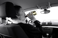 Drink and drive. Drunk driver with alcohol bottle drinking at the wheel Royalty Free Stock Images