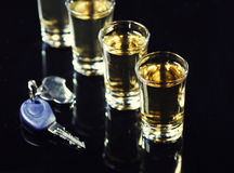 Drink and drive. Car keys in the foreground and a whiskey shots Royalty Free Stock Photo