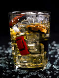 Drink and drive. Glass of whisky and several toy cars inside Royalty Free Stock Image