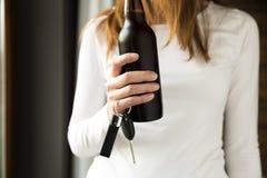 Drink en drijf geen concept De fles van de vrouwenholding bier en Royalty-vrije Stock Afbeeldingen