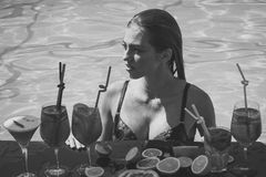 Drink and food. Swimming and relax in water pool. Summer vacation and party. Cocktail and sexy girl in pool. Woman with alcoholic beverage and fruit Royalty Free Stock Image
