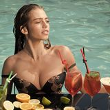 Drink, food and happiness. Woman with alcoholic beverage and fruit. Cocktail and sexy girl in pool. Summer vacation and party. Swimming and relax in water pool Stock Photography