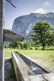 Drink fountain in Alps with mountains. Picture of a drink fountain with running water in the Austrian Alps with mountains and trees in summer stock photos