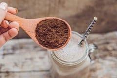 Drink från carob- och kerobpulver i en träsked Arkivfoton