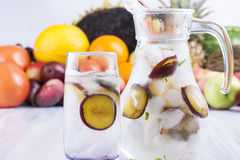 Drink. Fresh fruit and water drink with a purple plums slices, mint herb and ice cubes with some fruits in the background Royalty Free Stock Image