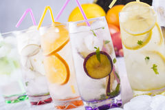 Drink. Fresh fruit and water drink with a sliced fruits - kiwi, pears, orange, plums, lemon, mint herb and ice cubes with some fruits in the background Stock Photography