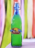 Drink in glass bottle on a vivid background. Lemonade  in blue glass bottle on a vivid background Royalty Free Stock Images