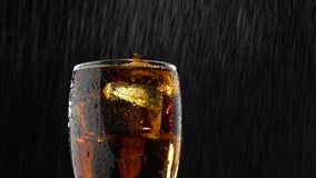 Drink into a glass with ice and drip drops of water . Black background stock footage