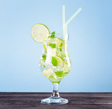 Glass of mojito cocktail on pastel blue background royalty free stock photo