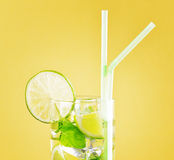 Glass of mojito cocktail on pastel yellow backgrou Royalty Free Stock Photo