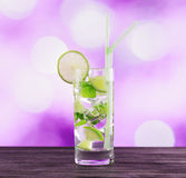 Glass of mojito cocktail on pink background Stock Images
