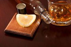 Drink. A glass of whiskey with ice, a slice of lemon and a bottle on the table Royalty Free Stock Image