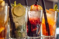 Drink här Coctaildrinkar tjänade som i exponeringsglas med dricka sugrör Alkoholisten blandade drinkar med is Med is drinkar in arkivfoto