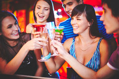 Drink for happiness. Happy friends with champagne cheering up at party royalty free stock photography