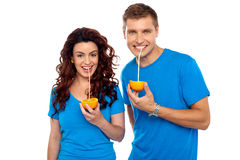 Drink healthy, stay healthy. Attractive couple drinking fresh orange juice royalty free stock photography