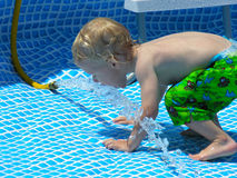 Drink from the hose. A two year old boy drinks from the hose while the pool is filling up Royalty Free Stock Images