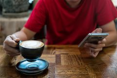 Drink hot coffee and play smartphone. Man in cafe using smartphone to chat and play social media and drinking hot coffee. Cup of Latte art on male hand with copy Stock Photography