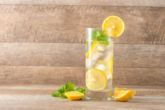 Drink for hot summer days. Fresh lime and lemon lemonade with mi. Nt in a glass on a wooden desk Stock Photo