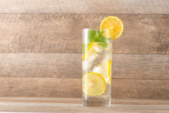 Drink for hot summer days. Fresh lime and lemon lemonade with mi. Nt in a glass on a wooden desk Royalty Free Stock Photos
