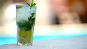 Drink i ett exponeringsglas på stranden stock video