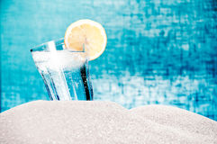 Drink with ice & lemon on the beach in the summer. A drink with ice and lemon on the beach in the summer on blue background Royalty Free Stock Photography