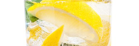 Drink of ice, the lobules of fresh juicy yellow lemon and crystal water in a glass. stock photos