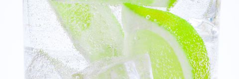 Drink from ice, lumps of f juicy green lime and crystal clear water in a glass. Drink from ice, lumps of fresh juicy green lime and crystal clear water in a stock photos
