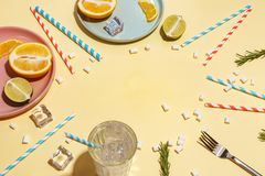 Drink with ice with paper cocktail tubes and fruit on a yellow background. Table setting stock photography