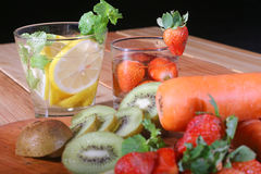 Drink from the juice of fruits such as melons, strawberries, kiwi, carrots, with a black background Royalty Free Stock Photo
